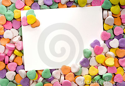 Blank note card surrounded, framed by candy hearts