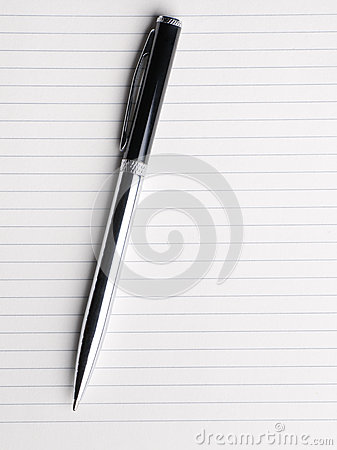 Blank notebook paper with pen. isolated on white.
