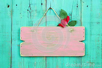 Blank pink weathered sign with red flower hanging on antique green wood door