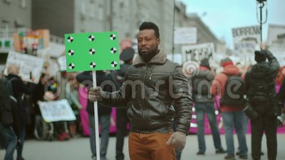 Blank placard political protest. Tracking point green screen. Political rally 4k. African american man. Empty banner in hand. Tracking point. Copy space. Blank stock video