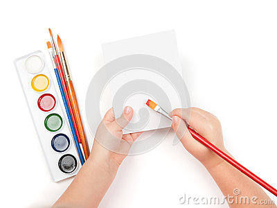 Blank sheet in child hand with paintbrush
