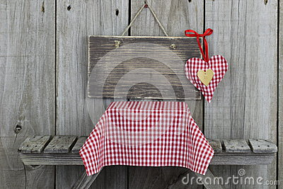 Blank wood sign with red heart over picnic table