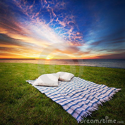 Blanket and pillows on grass