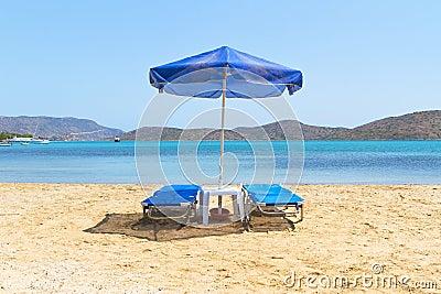 Blaue deckchairs unter Sonnenschirm
