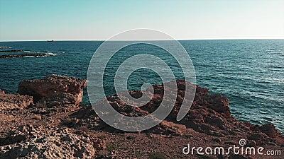 Blauw oceaanwater en bruine rotsachtige klippen met zon op horizon Koraalstrand in Cyprus Satellietbeeld van blauw oceaanwater di stock videobeelden
