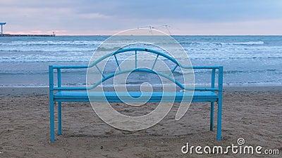 Blauwe bank op het zandige strand bij zonsondergang Geschikte infrastructuur voor het ontspannen door het overzees Overzeese golf stock video