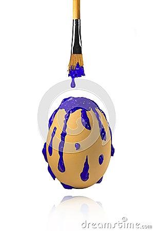 Blauwe verf die van borstel op het ei druipen