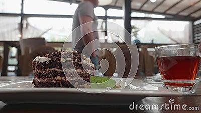 Blickwinkel männliche Hand abbrechen mit Löffelschokoladenkuchen am Tisch. Nahe Mann trinkt schwarzen Tee mit stock footage