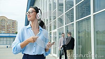 Blij dat kantoormedewerker in hoofdtelefoon geniet van muziek met smartphone buiten stock videobeelden