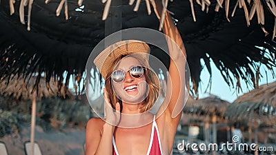 Blij dat modesmeisje in bikini een leuke poets heeft met palmparaplu op het strand bij de close-up stock videobeelden