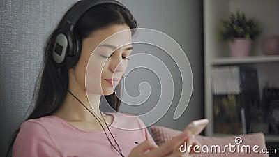 Blij dat tien naar muziek luistert die thuis op een sofa ontspannen is stock footage