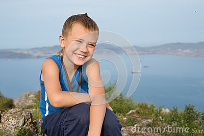 Blije jongen bovenop een berg
