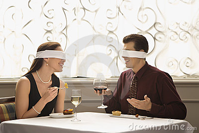Blindfold couple dining
