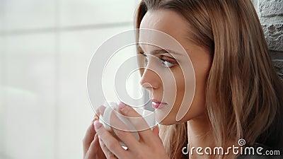 Bliska twarz spokojnej młodej kobiety pijącej gorący napój z kubka patrzącego przez okno zbiory