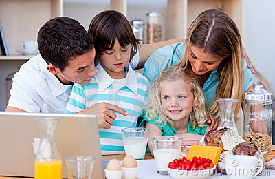 Blissful family using laptop during the breakfast