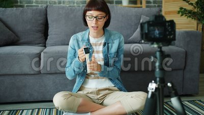 Blogueira feminina gravando vídeo sobre relógio digital usando câmera no apartamento filme