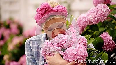 blommar kvinnor Kvinnor att bry sig blommor 4K Lyckliga kvinnor i blommaträdgård Kvinnan tycker om blommor arkivfilmer
