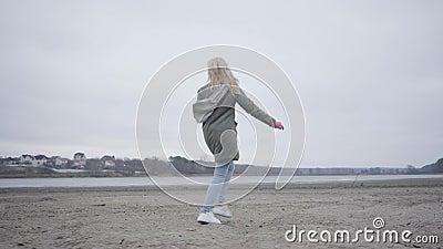 Blond blanke vrouw in warme kleren op het strand van het najaar Joyful girl die plezier heeft in rivier- of meeroever stock video
