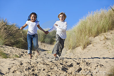 Blond Boy & Mixed Race Girl Running At Beach