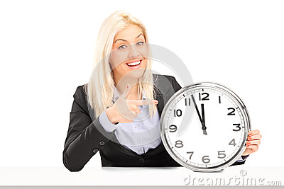Blond businesswoman sitting and pointing on a wall clock