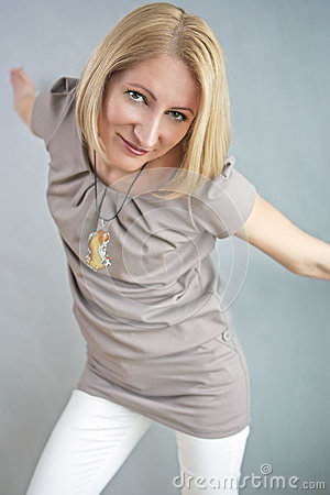 Blond caucasian woman posing over gray wall