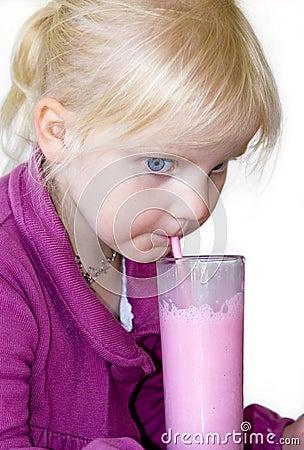 Blond child drinking milkshake