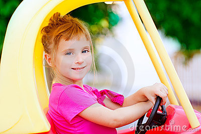 Blond children girl driving toy car
