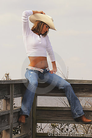 Blond cowgirl on fence in hat