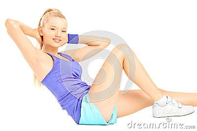 Blond female exercising abs on floor