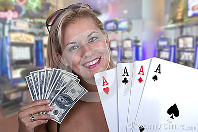 Blond Female model smiling while holding a poker hand of four ac