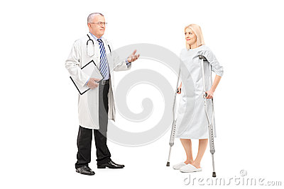 Blond female patient in hospital gown with crutches and medical