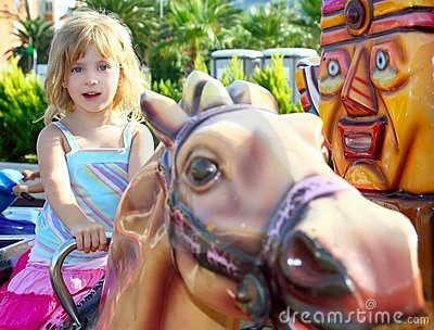 Blond girl with fairground horse enjoy in park