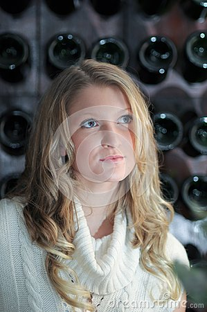 Blond girl in front of wine rack