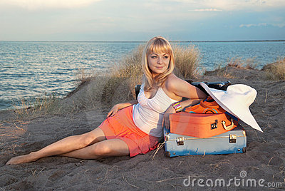 Blond girl with her luggage on the beach