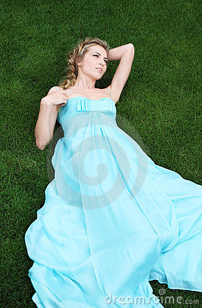 Blond girl in the long dress in the garden