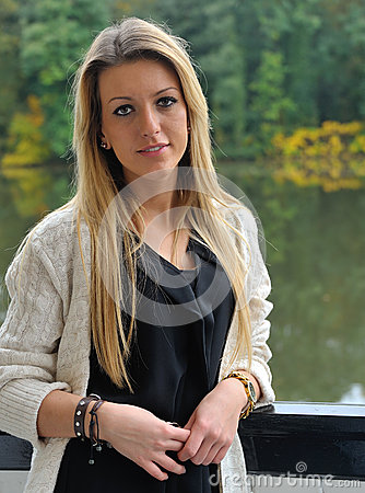 Blond girl standing near lake