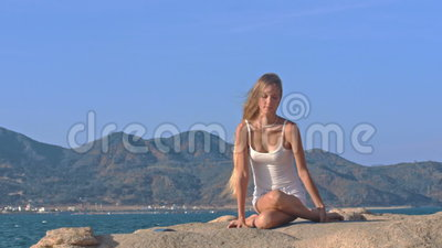 blond girl in top sits in lotus yoga pose hands behind
