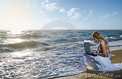 Blond girl using laptop on  sea