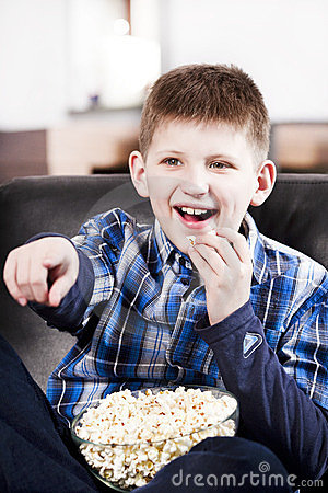 Blond happy boy watching tv and eating popcorn