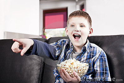 http://thumbs.dreamstime.com/x/blond-happy-boy-watching-tv-eating-popcorn-24012468.jpg