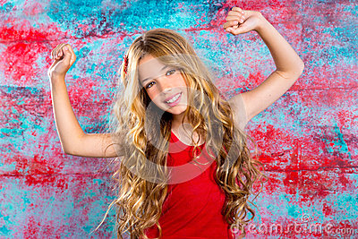 Blond happy children girl in red happy arms up