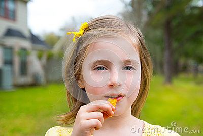 Blond kid girl eating corn snacks in outdoor park