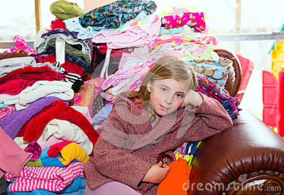 Blond kid girl sitting on a messy clothes sofa