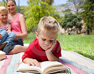 Blond little boy reading at a picnic