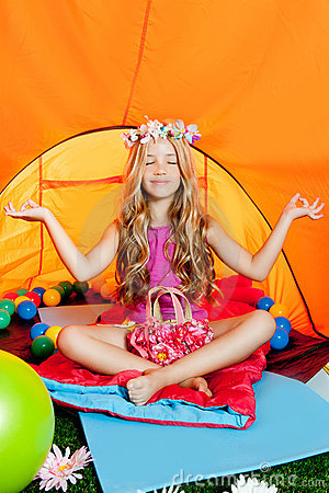 Blond little girl practicing yoga in camping tent