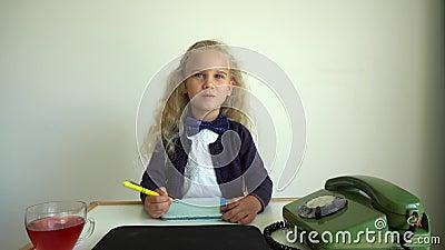 Blond-Mädchen, das Sekretärin spielt Kinder sitzen am Tisch mit Retro-Telefon Gimbal-Bewegung stock footage