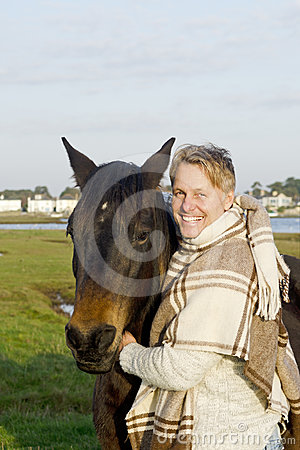 A blond man with his brown horse.