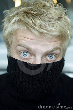 Blond man pull on black sweater