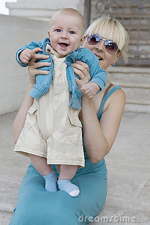 Blond mother holding  her smiling baby