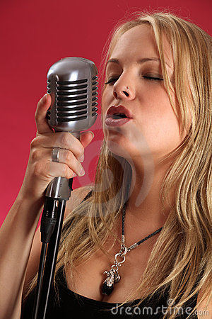 Blond singing into retro microphone